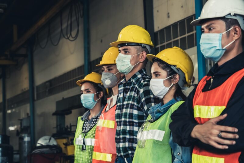five workers lined up in hardhats, safety vests, and face masks