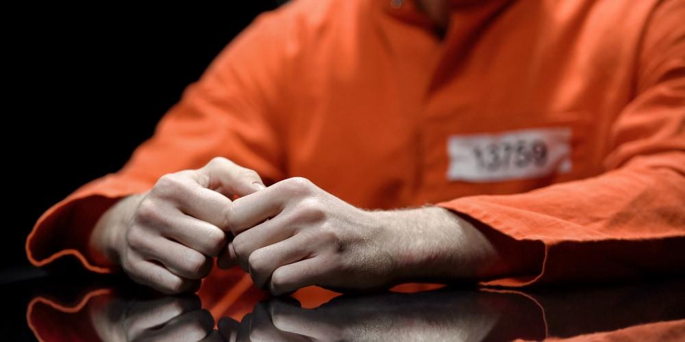 prisoner in orange uniform sitting at table