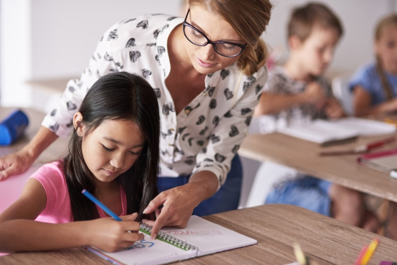 female teacher helping young girl with writing